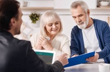 Real estate advisor working with aged couple