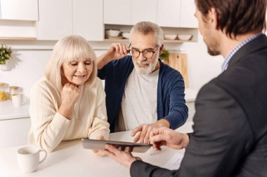couple using gadget with real estate agent