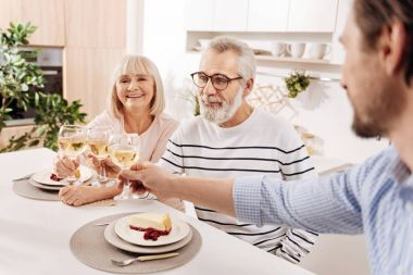 Smiling elderly couple relishing dinner with their child at home