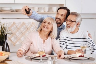 man taking selfie with aged parents at home