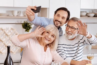 Smiling man taking selfie with senior parents