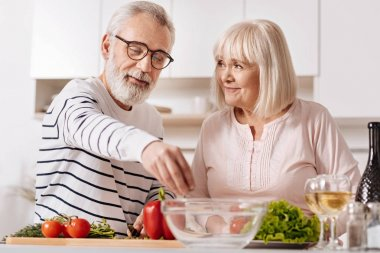 Optimistic aged couple cooking together