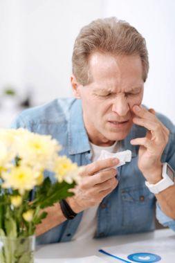 Disturbed man having allergy on flowers