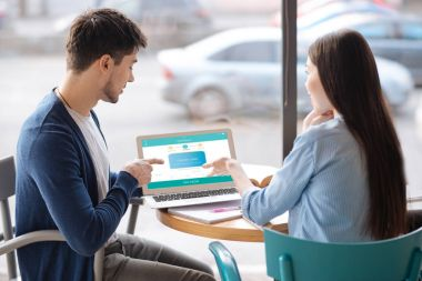 Young guy presenting information from laptop