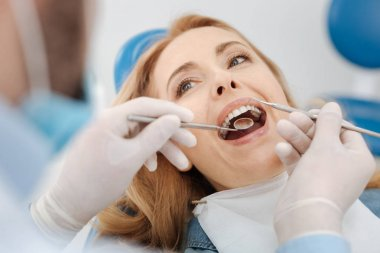 Scrupulous competent dentist cleaning patients teeth