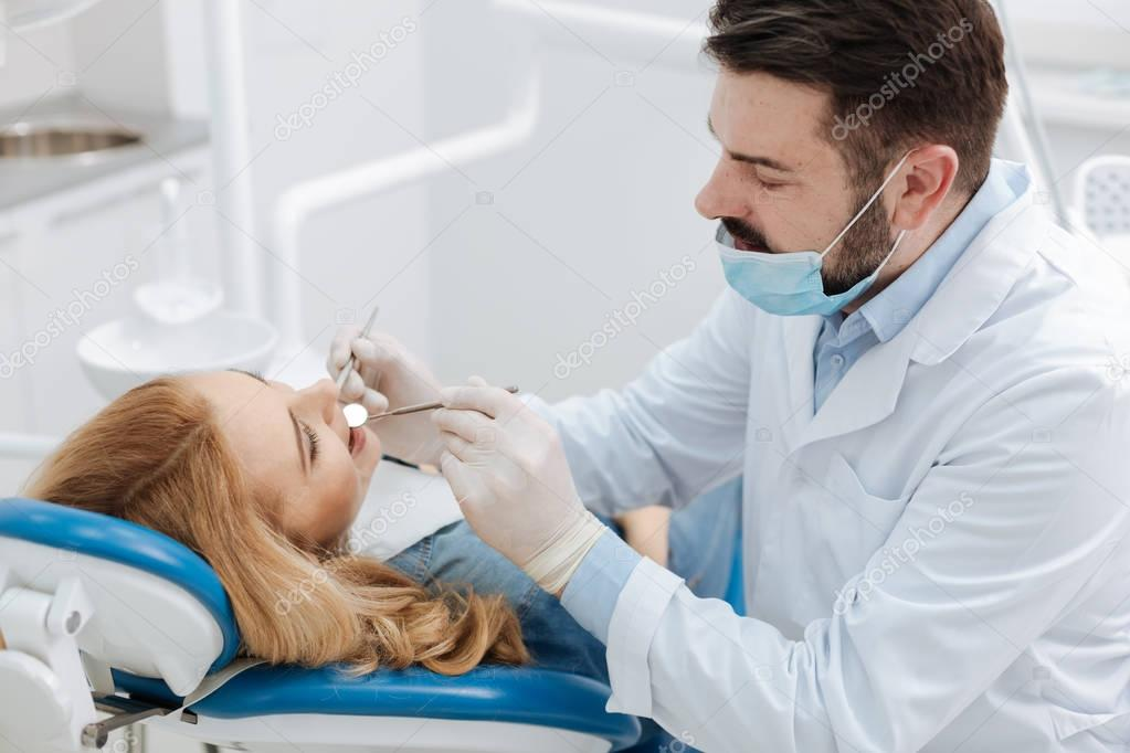Skillful lovely dentist being very careful