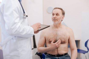 Surprised senior patient explaining something