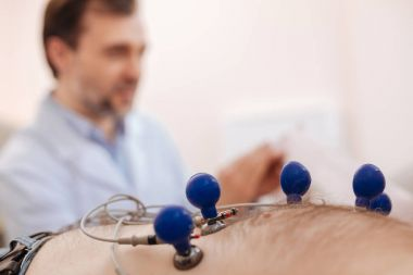 Experienced cardiologist attaching sensors to patients chest