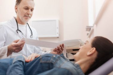 Optimistic cardiologist having some good news for young lady