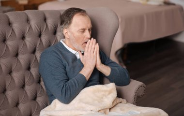 Old man coughing while sitting on couch