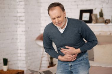 Old man feeling big discomfort in stomach.