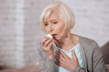 Closeup of elderly coughing woman