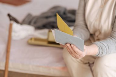 Close up of envelopes being in hands of an aged woman