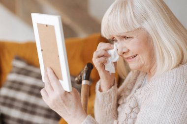I dont now how to live now. Miserable depressed elderly woman holding a paper tissue and crying while seeing the photo of her husband stock vector