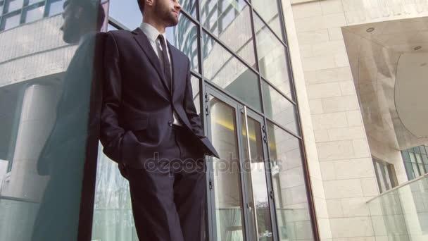 podnikatel, stojící poblíž kancelářská budova