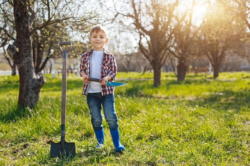 Happy little kid posing for picture in garden