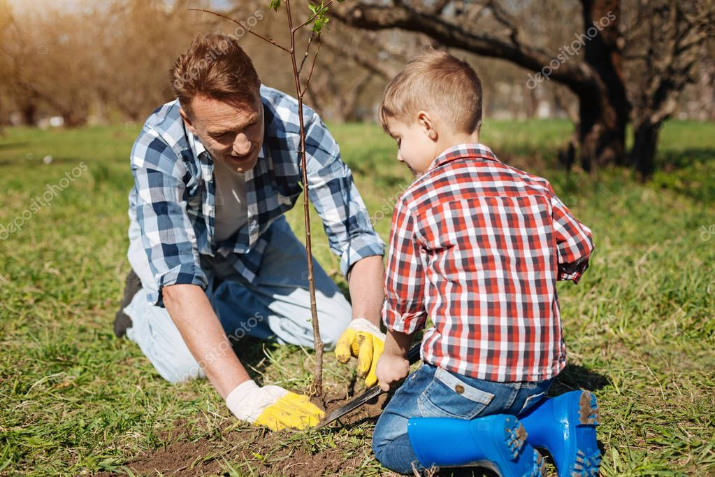 Little kid and his father gardening together