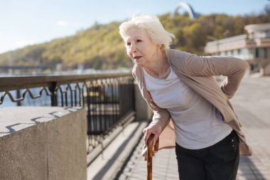Frustrated woman worrying about her back on the street