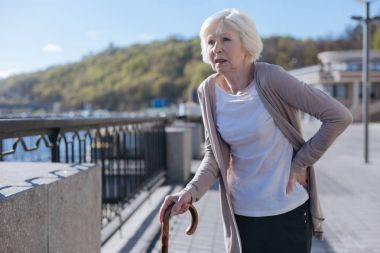 Retired woman having lower back pain during the promenade