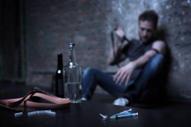 Desperate addict pricking veins in the dark basement