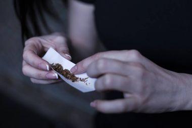 Skilled drug user turning tight marijuana cigarette outdoors