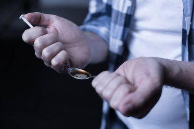 Criminal heroin addict preparing drug dose in the dark place
