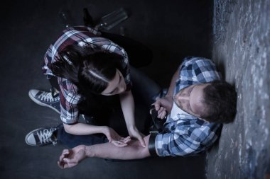 Helpful addicts making heroin injection in the dark place