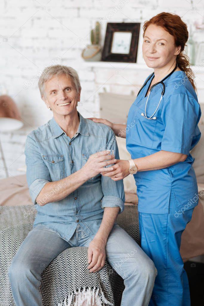 Proficient nurse providing medical assistance for elderly people
