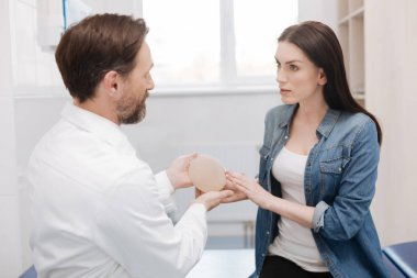 Wise admirable woman asking about details of plastic surgery