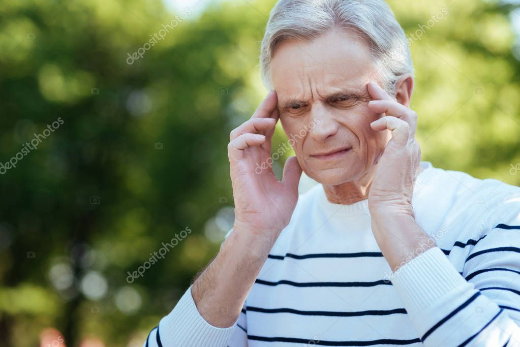 Confused pensioner feeling terrible headache outdoors