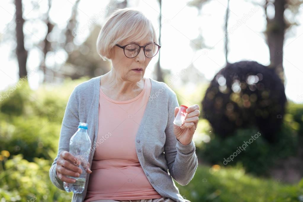 Attentive woman taking pills in the park
