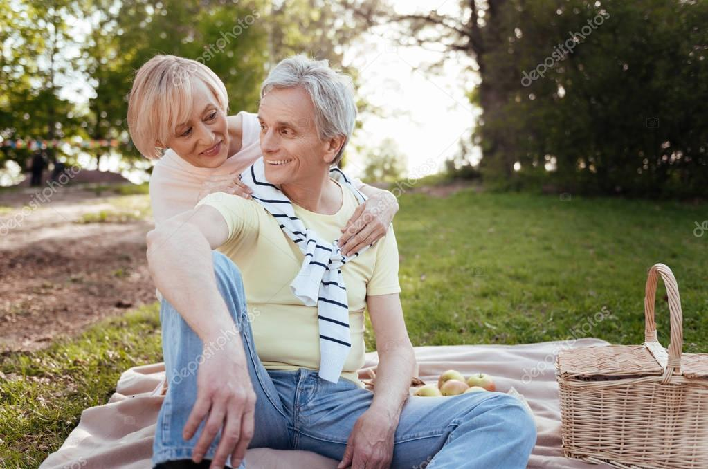 Optimistic aging couple sharing positivity at the picnic