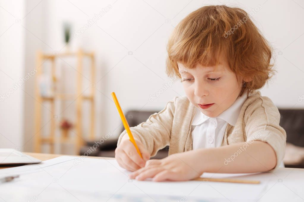 Very concentrated boy drawing picture