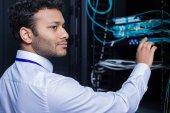 Vážně příjemné muž pracuje v serverové místnosti