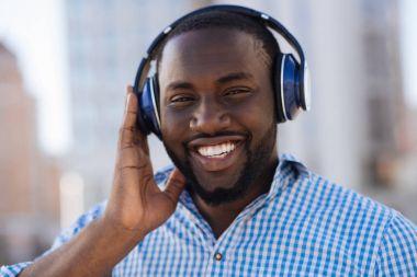 Energetic pleasant man enjoying his playlist while walking