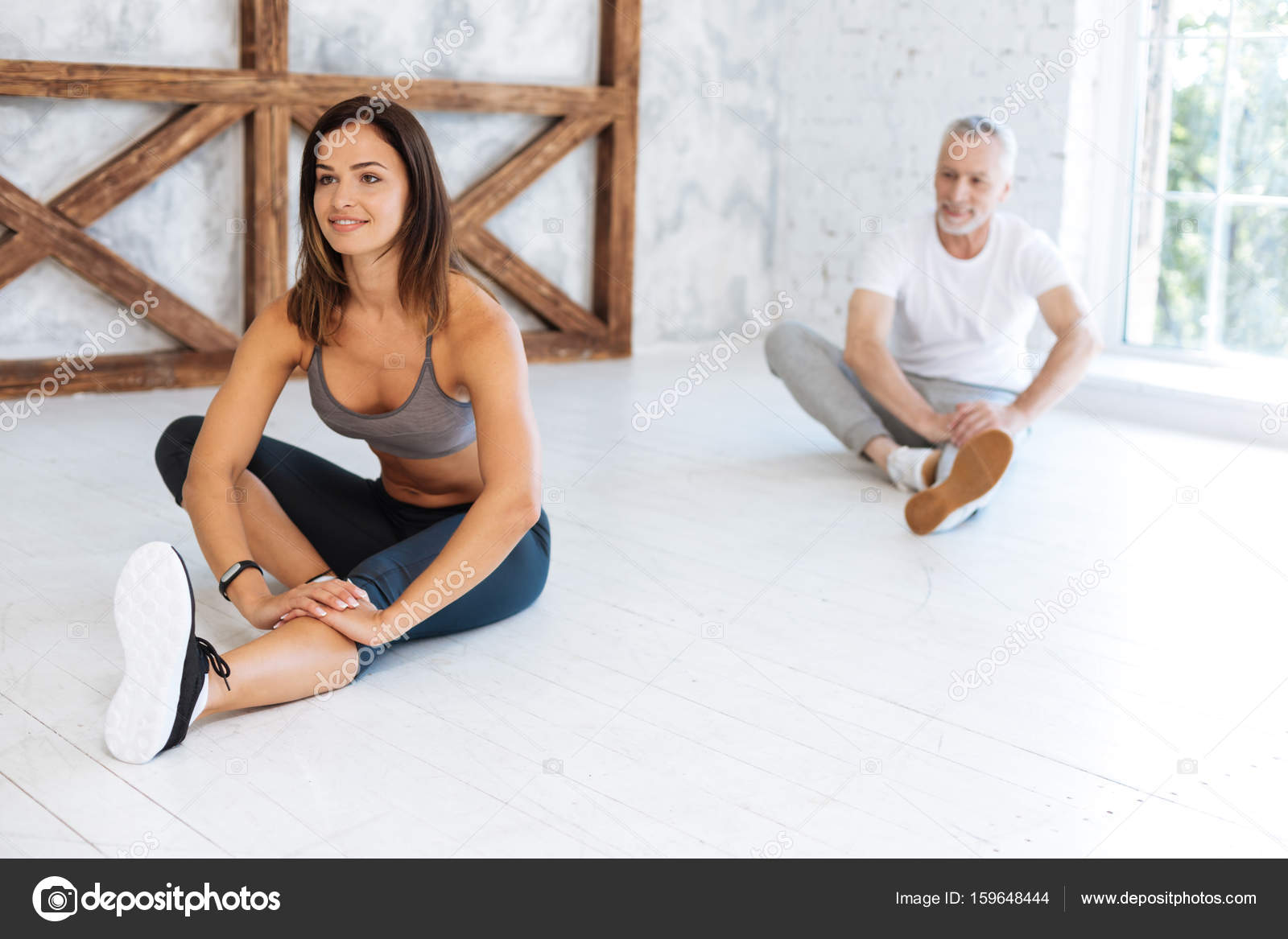 Attractive woman sitting on the floor and keeping her back straight while  leaning hands on the knee — Photo by ...