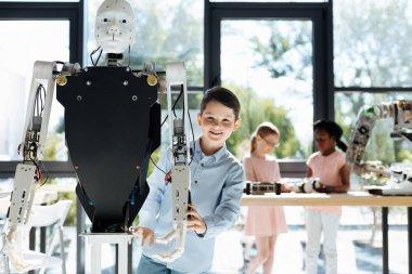 Dark-haired boy standing near a human robot