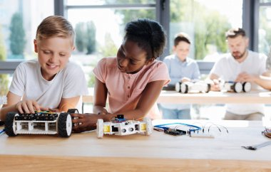 Girl examining the wheel of her friends robotic vehicle