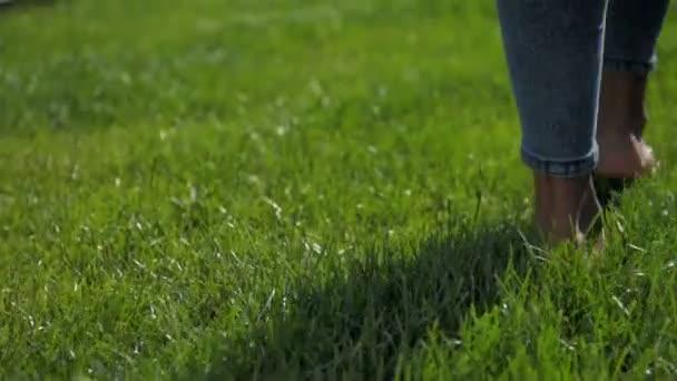 Zblízka bosý mladé dívky chůze po trávě