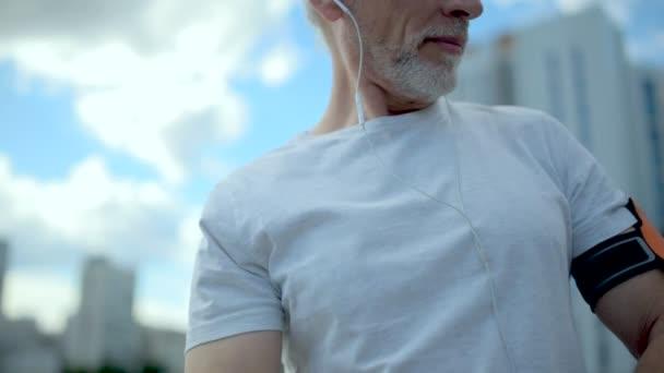 angenehmer älterer, sportlicher Mann hört Musik