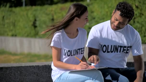 Positiven internationalen Freiwilligen sitzen im park