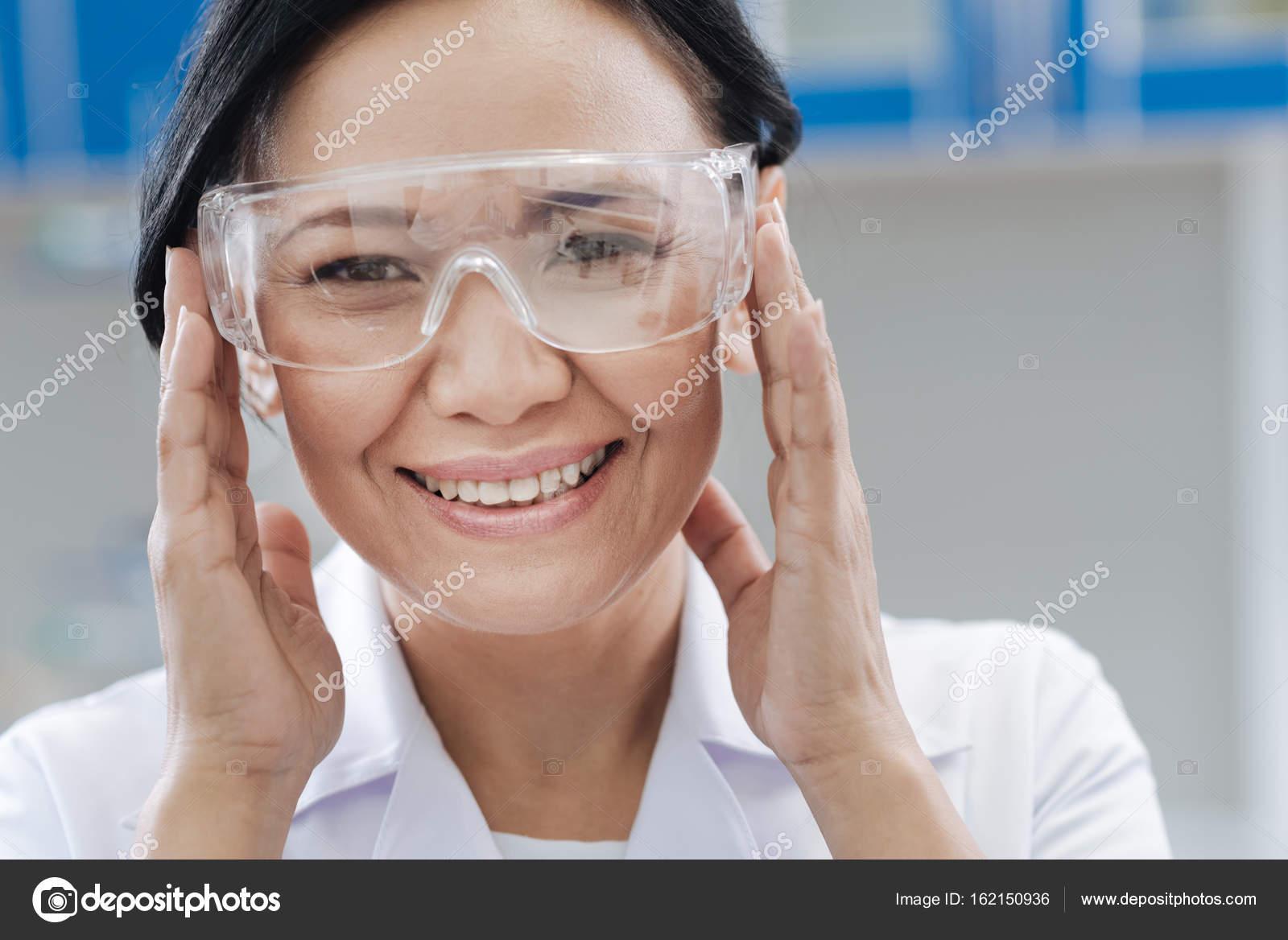 Scientifique de laboratoire positif ravi souriant et fixant ses lunettes de  protection tout en étant prêt à travailler — Image de Dmyrto Z 90cc7fa834f7