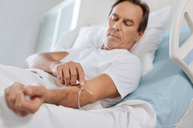 Pleasant nice man looking at his catheter
