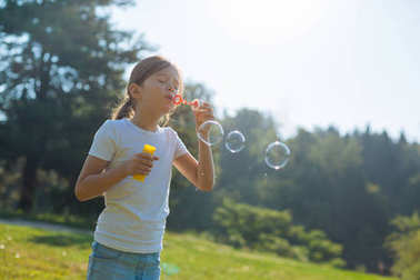 Adorable little girl blowing soap bubbles outdoors
