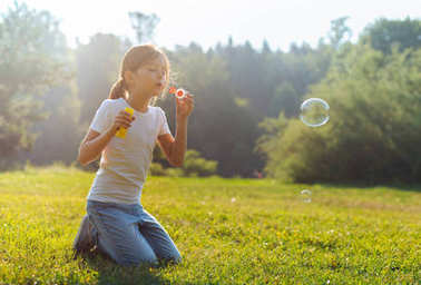 Little girl blowing bubbles in the meadow