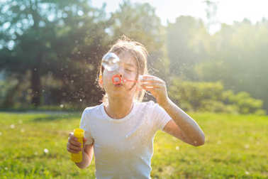 Portrait of little girl blowing soap bubbles outdoors