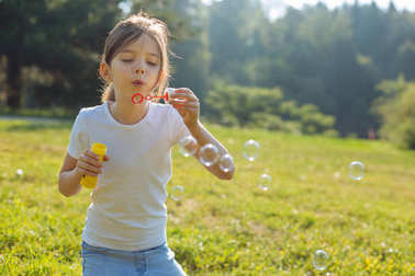Cute little girl blowing soap bubbles in the forest