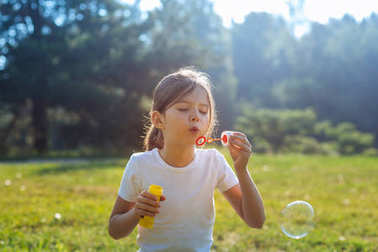 Pleasant little girl playing with soap bubbles