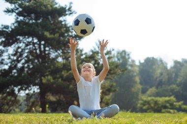 Upbeat girl throwing a ball in the air