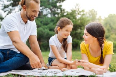 Happy family doing puzzle on picnic